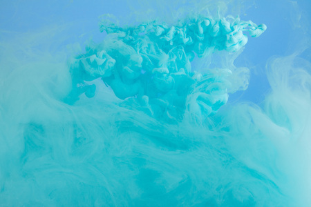 Close up view of turquoise watercolor paint swirls isolated on blue