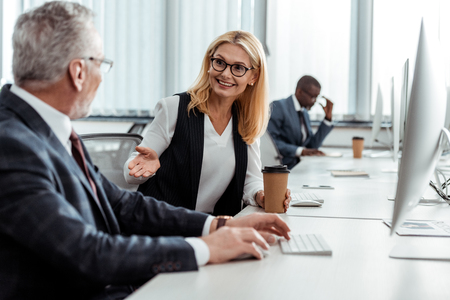 selective focus of cheerful blonde woman holding paper cup and gesturing while looking at man in office Stok Fotoğraf