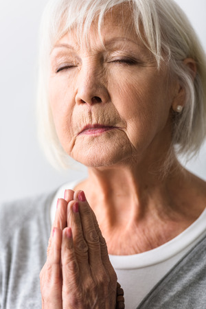 senior woman showing please gesture and praying with closed eyes