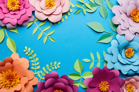 top view of multicolored paper cut flowers with leaves on blue background with copy space Stock Photo