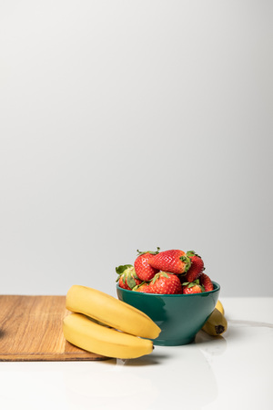 sweet strawberries in bowl near yellow bananas and cutting board on grey Stock Photo