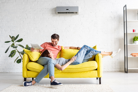 happy man with smiling girlfriend relaxing on yellow sofa under air conditioner at home Stockfoto