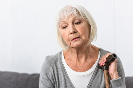 pensive senior woman with wooden cane looking down Stockfoto