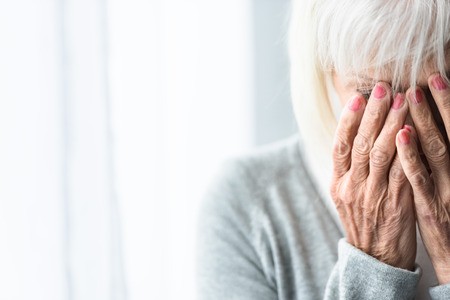 partial view of crying senior woman covering face with hands Foto de archivo