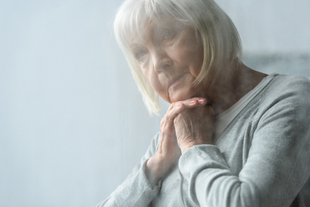 selective focus of pensive senior woman with grey hair propping face with hands