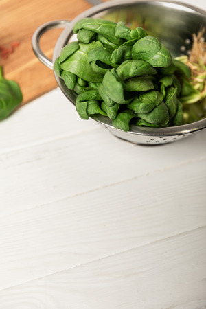 fresh green and organic spinach leaves in colander on white surface Stock Photo