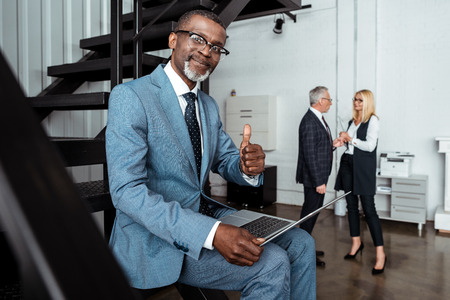 selective focus of cheerful african american man showing thumb up near partners in office Stock fotó