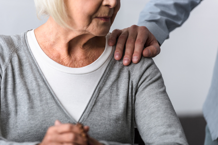 partial view of man supporting senior mother with grey hair