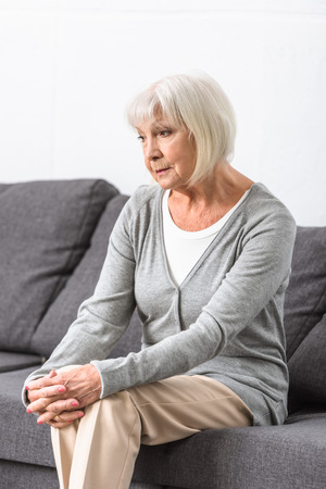 pensive senior woman with grey hair sitting on sofa in living room