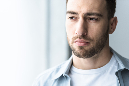pensive bearded man in shirt looking away at home Stockfoto