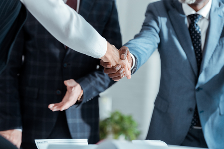 cropped view of african american businessman and businesswoman shaking hands in office