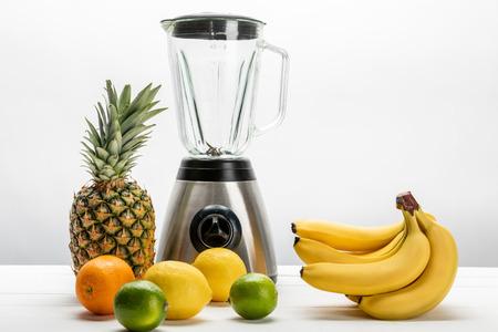 blender near yellow bananas, ripe pineapple, lemons, orange and limes on white
