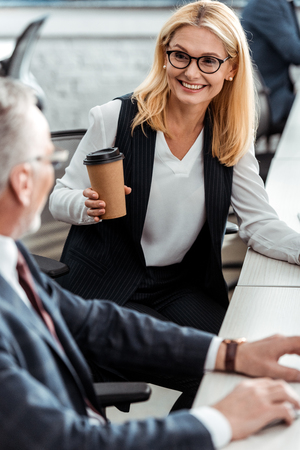 selective focus of attractive blonde woman smiling while holding paper cup and looking at coworker in office