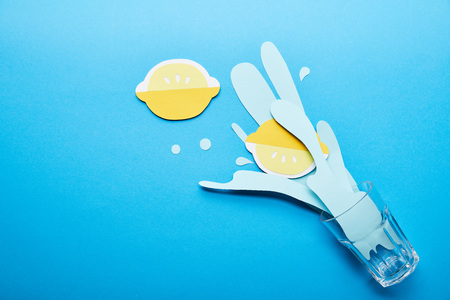 top view of glass with paper cut water splash and lemons on blue background with copy space
