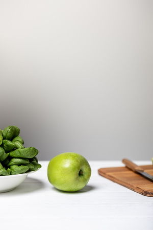 plate with spinach leaves near green apple and cutting board on grey Stock Photo