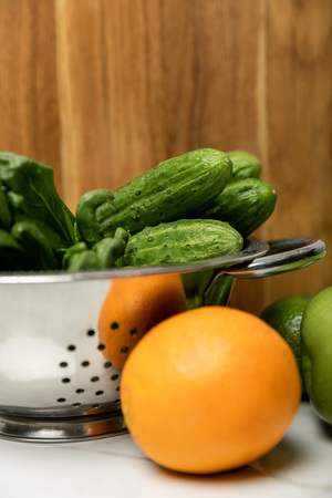 selective focus of green cucumbers in colander near orange and wooden cutting board Stock Photo