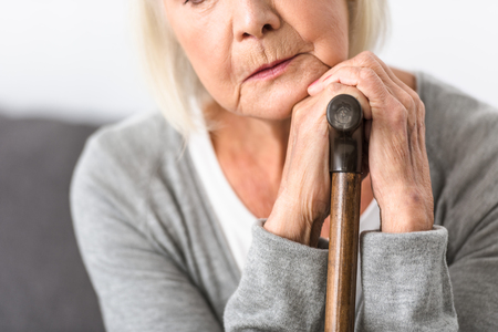 cropped view of pensive senior woman with wooden cane