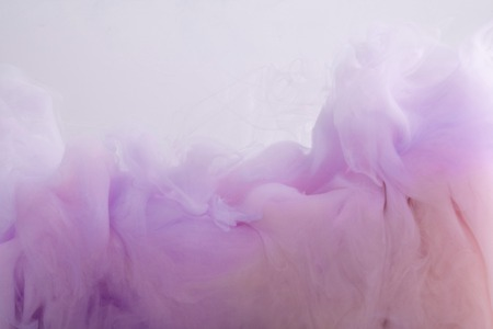 Close up view of pink and purple paint mixing in water 写真素材