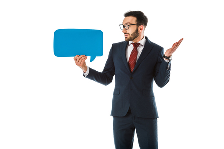 discouraged businessman showing shrug gesture and looking at speech bubble isolated on white