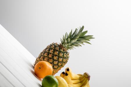 ripe pineapple, lemon, orange and lime near bananas on white