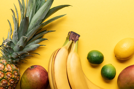 top view of whole ripe bananas, pineapple, citrus fruits and mango on yellow background with copy space