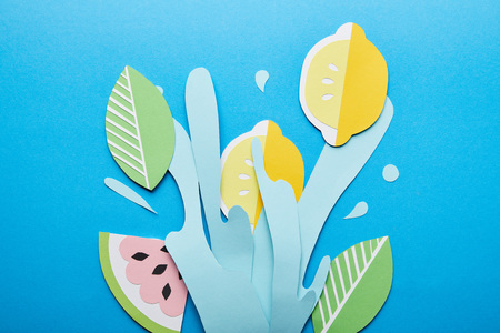 top view of paper cut water splash with lemons, leaves and watermelon on bright blue background Banco de Imagens