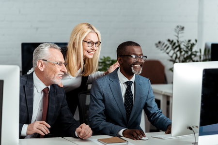 happy blonde businesswoman looking at computer monitor near multicultural businessmen Stock Photo