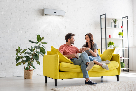 Feliz pareja joven hablando y sosteniendo tazas mientras está sentado en el sofá amarillo bajo el aire acondicionado en casa