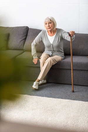 senior woman with walking stick sitting on sofa in living room