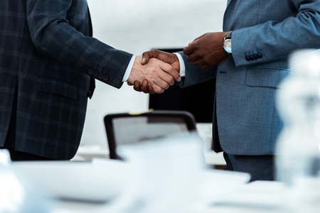 cropped view of african american businessman shaking hands with partner in office
