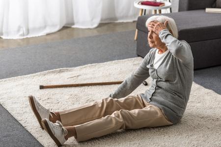 Mujer mayor con migraña sentada sobre una alfombra y tocando la frente con la mano Foto de archivo