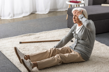senior woman with migraine sitting on carpet and touching forehead with hand Archivio Fotografico - 124626294