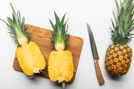 top view of cut ripe yellow pineapple on wooden chopping board near whole fruit and knife on white background