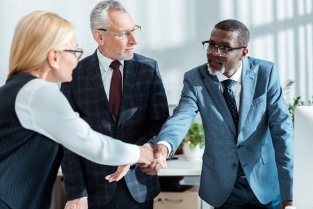 selective focus of businessman in glasses looking at handsome african american man shaking hands with blonde woman in office