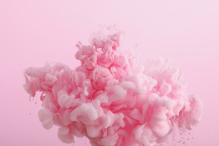 Close up view of pink smoky paint in water isolated on pink