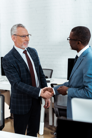 selective focus of cheerful businessman in glasses shaking hands with african american partner Imagens
