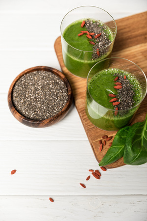 top view of chia seeds in bowl near glasses of green smoothie on white