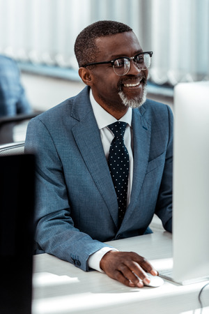 selective focus of happy african american businessman looking at computer monitor in office Stock Photo