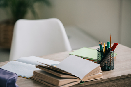 selective focus of wooden desk with open book, copy books and stationery
