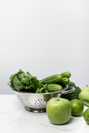 green apple near tasty vegetables and spinach leaves on white