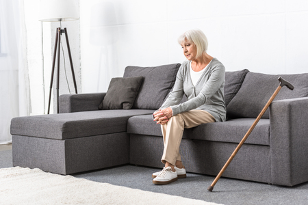 pensive senior woman with wooden cane sitting on sofa in living room