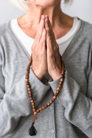 partial view of senior woman praying with wooden rosary Stok Fotoğraf - 124626500