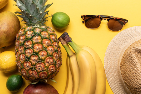 top view of whole ripe exotic fruits and summer accessories on yellow background Stock fotó
