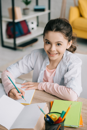cheerful schoolkid writing in notebook and smiling at camera while doing homework