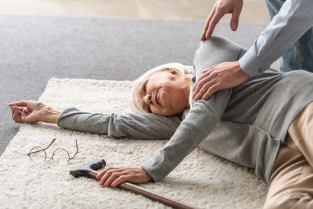 cropped view of man helping senior mother with heart attack fallen on carpet Stockfoto