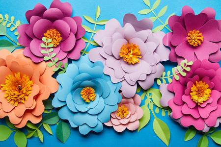 Vista superior de flores cortadas de papel de colores brillantes con hojas verdes sobre fondo azul.
