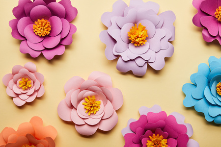 top view of colorful paper cut flowers on beige background