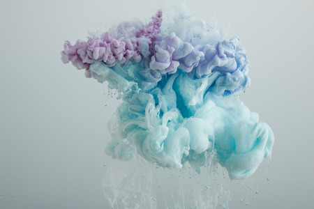 Close up view of light blue, pink and purple paint mixing isolated on grey Banque d'images - 124626534