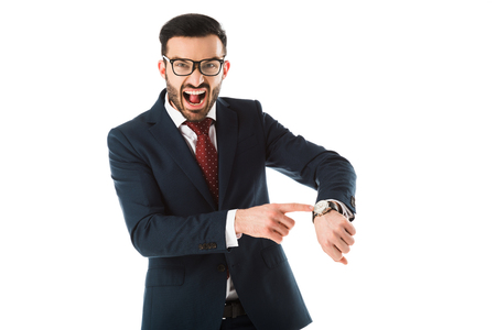 angry businessman quarreling while looking at camera and pointing at watch isolated on white Imagens