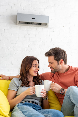 heureux couple souriant tenant des tasses assis sous le climatiseur à la maison